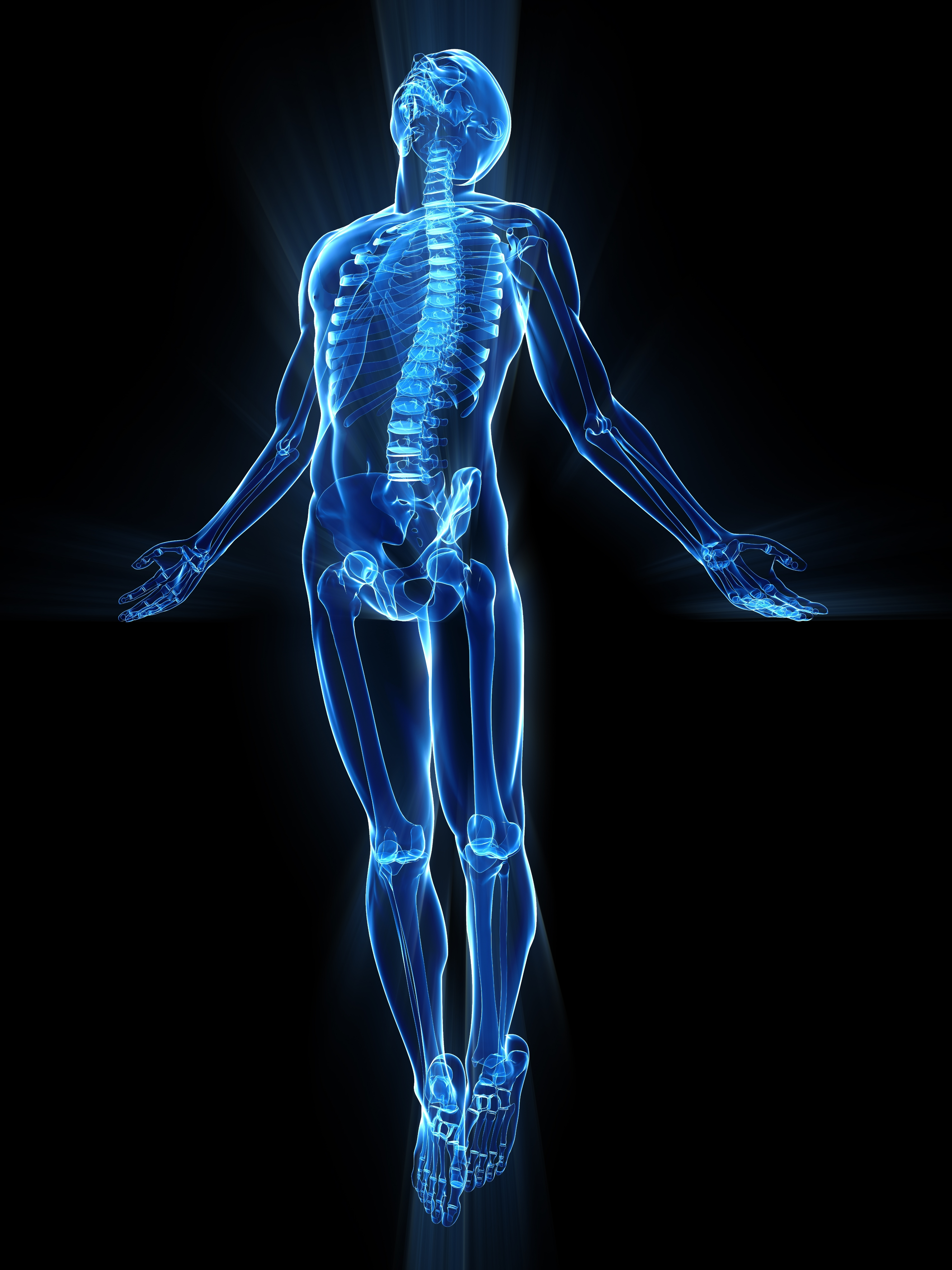 human body in xray format receiving electromagnetic pulses from PEMF therapy into his bones