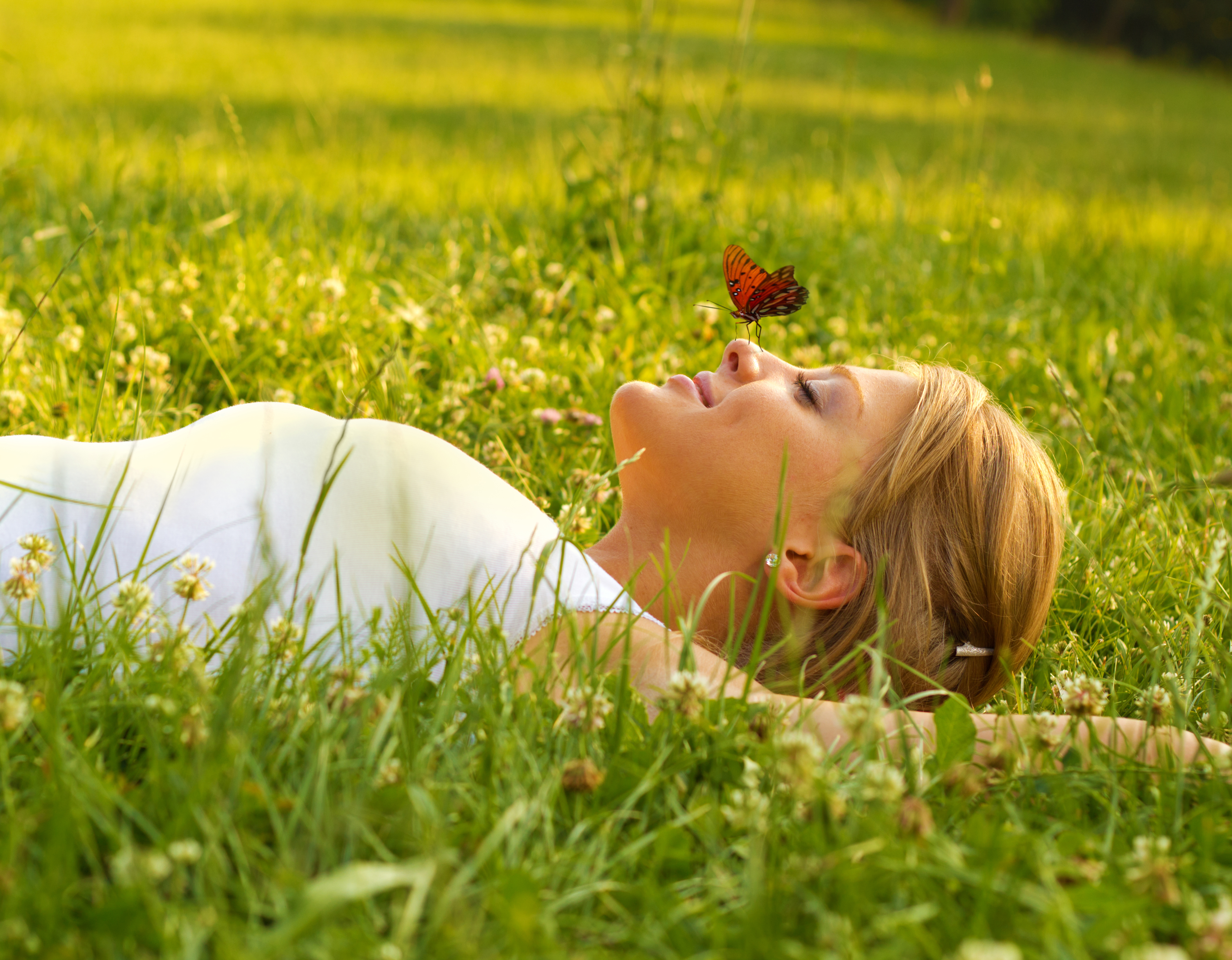 women laying down in the grass with acne free skin while using light therapy