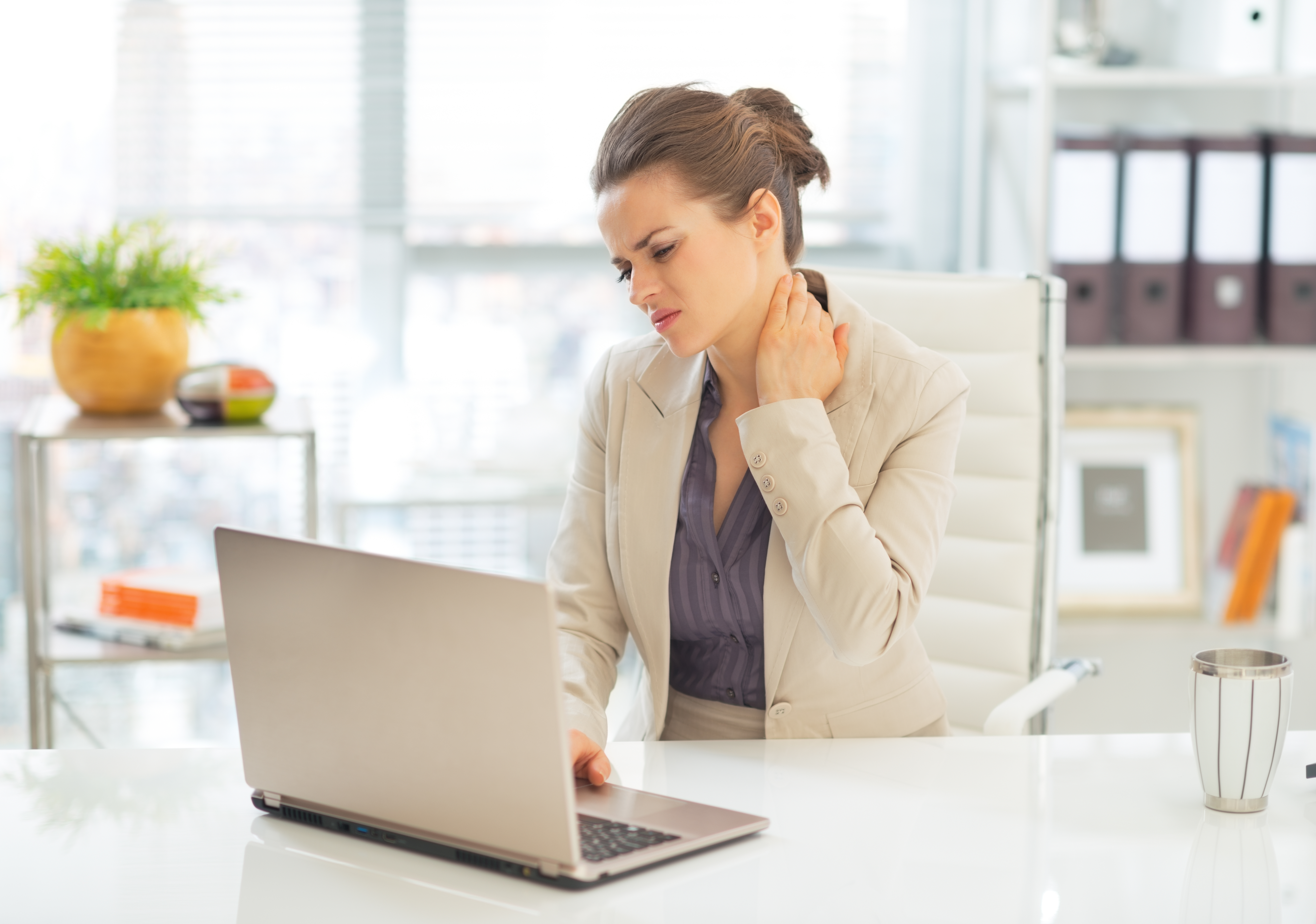 woman suffering from chronic pain in her neck while sitting at a computer